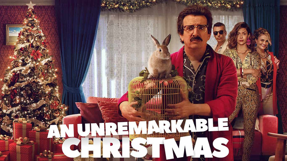 A Christmas stands with bright lights wrapped around it in the left corner of the frame; a window beside it which is covered in a lace curtain, creating a darker lighting to the photo. A man also stands in the centre holding a cage with a rabbit on top — he wears thick lenses and red and blue pajamas, his brown hair and moustache blending in with the darker lighting of the image.