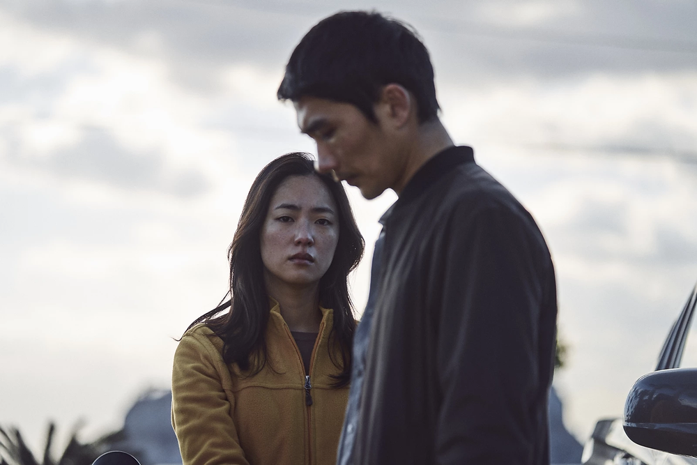 A woman stands at the left of this image, staring directly into the lens of the camera with tears in her eyes. She is gripping onto the arm of a man who stands on the right, his side facing the camera as he looks down with a saddened expression.