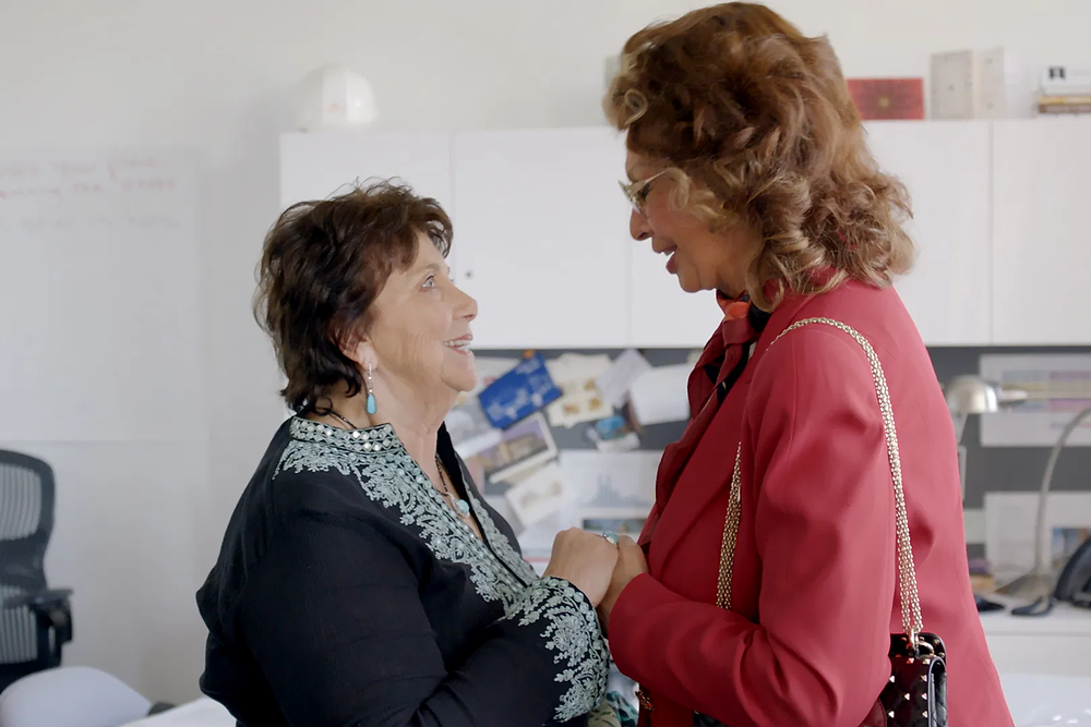 Kulik wears a dark blue shirt as she stands on the left, holding hands with the taller Loren who wears a bright pink jacket, as they stand in a room that is minimalist and completely white.