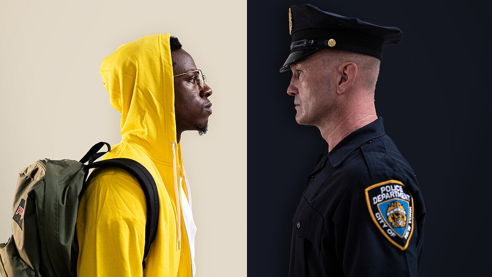 The image is split in two - the left sports a white background and the right a navy one. An officer stands the right, facing the man who stands in a bright yellow hoodie on the left.