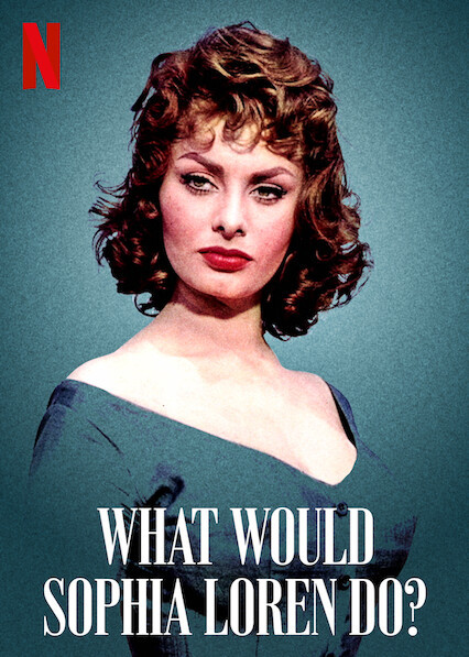 A young Sophia Loren stands in the centre of the image against a green/blue background, wearing an off the shoulder dress of the same colour. Her brown hair is short and curled as her red lipstick is the most prominent pop of colour to be seen.
