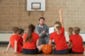 coach instructing youth girls basketball