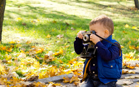 a small boy taking a picture with a camera
