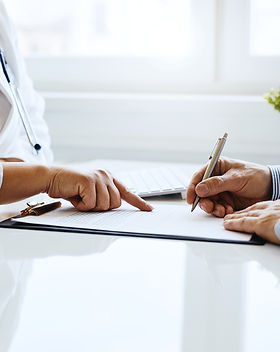 Patient signs a document with his doctor