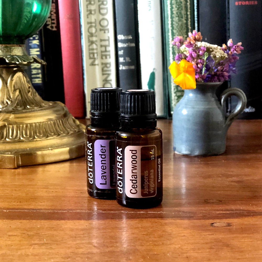 2 bottles of Lavender and Cedarwood essential oils near books and flowers in a study