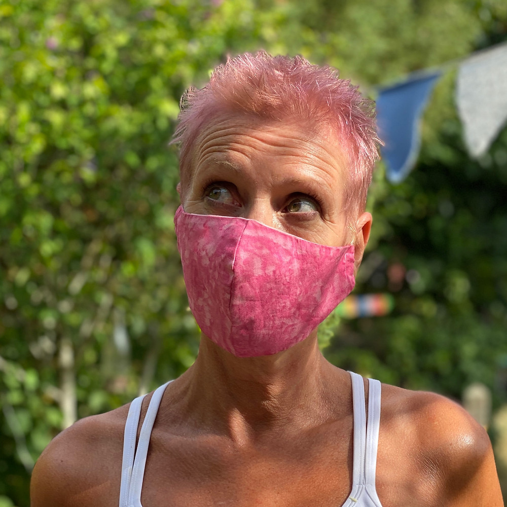 woman with pink hair wearing pink mask