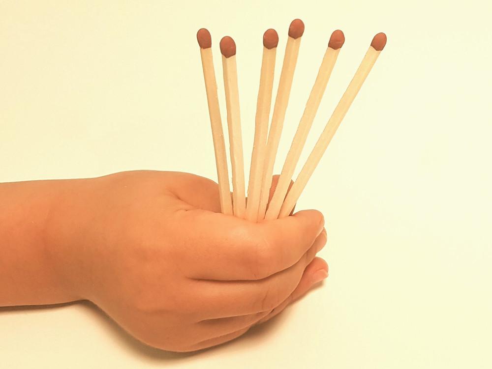 Eine Hand hält 6 Streichhölzer