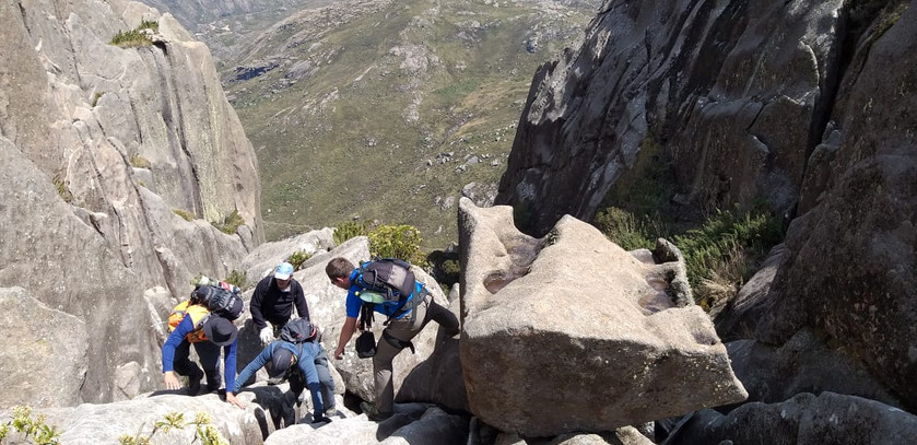 At the foot of the mountain, the trail turns into a steep ascent over and between rocks, then into a climb...