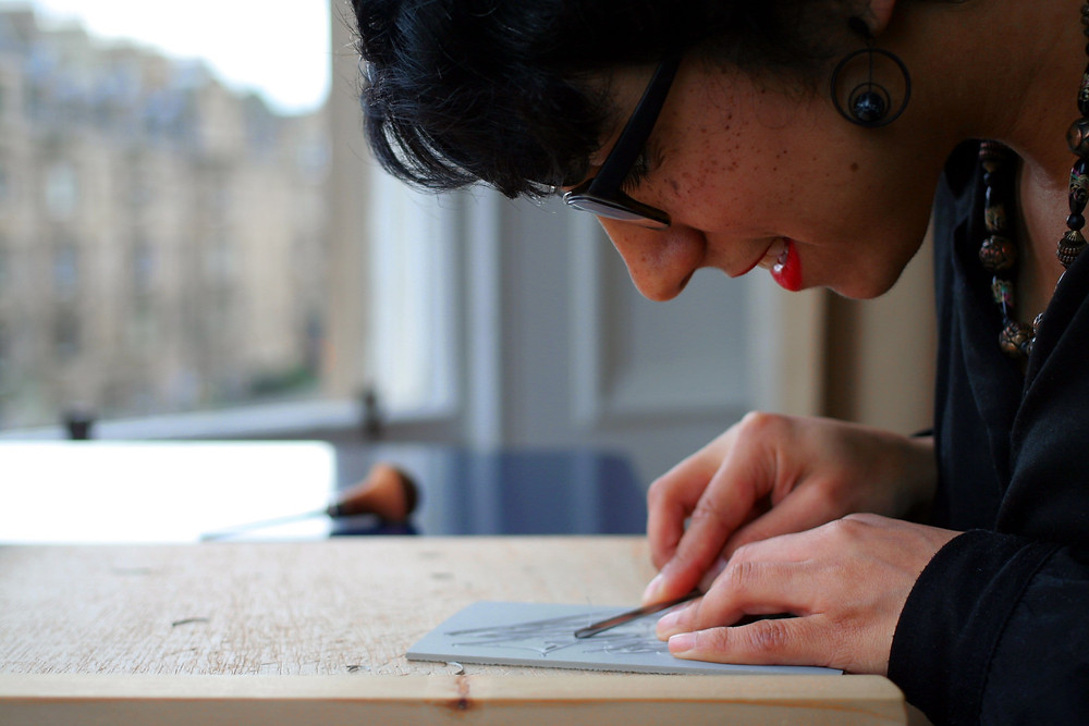 Woman focusing on lino cutting at an Unwind LDN workshop offering distraction and attention on one tasks at hand