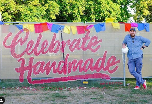 Jamie posing next to his completed giant mural made bespoke for the Handmade Festival 2019