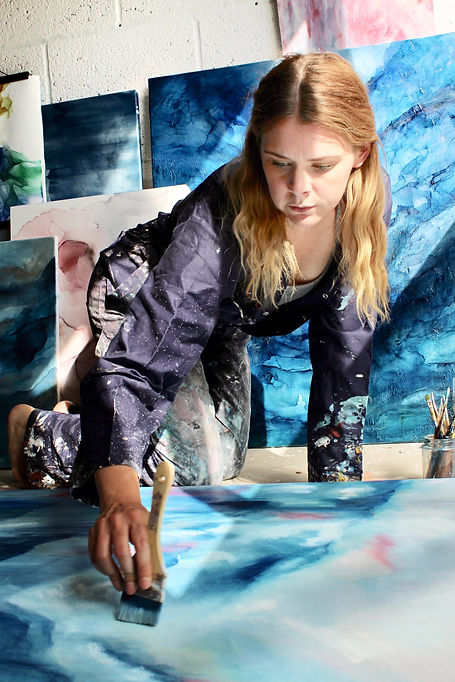 Christina Sadler in her studio painting large abstract art