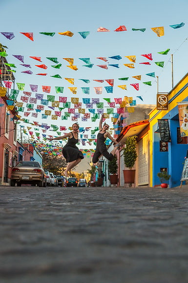 Two women jumping in the air under colorful banners in Jalatlaco, Oaxaca, Mexico.