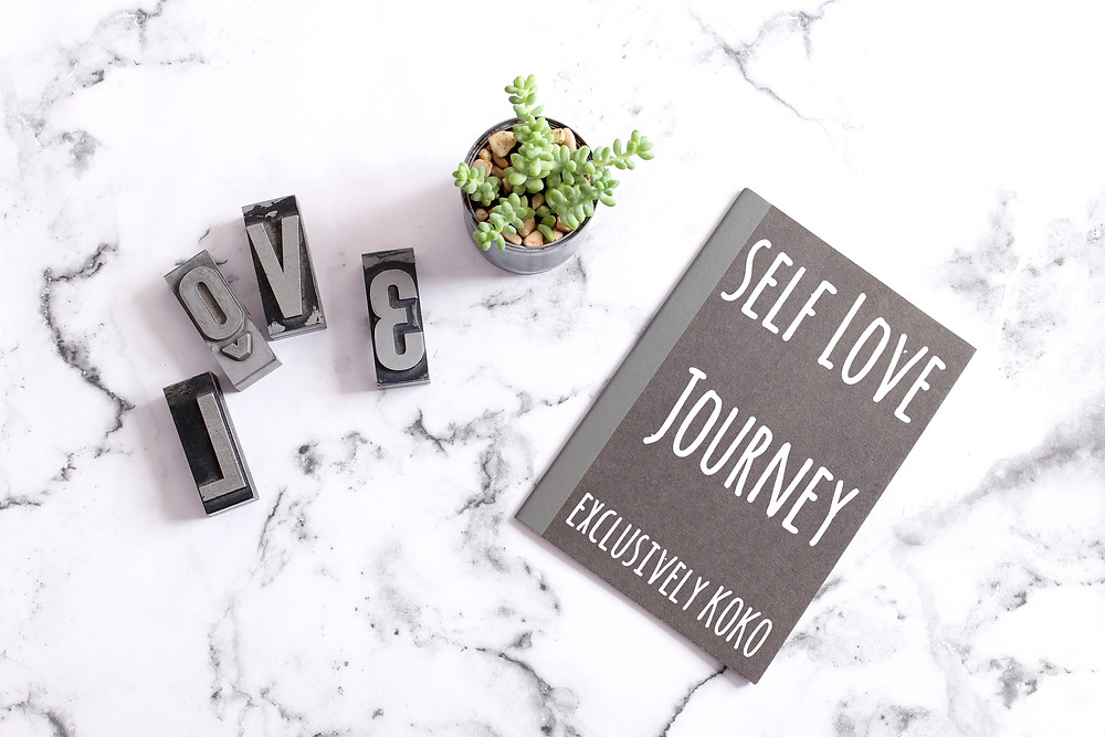 A book with Self love journey written on the cover and L O V E letter blocks kept beside it.
