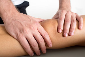 Physiotherapist's hands assessing client for preventing knee injuries.