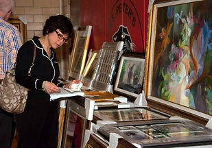 Woman looking at art during preview of a fundraising art auction