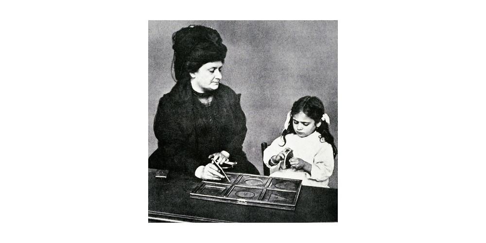 Maria Montessori avec un enfant jouant à reconnaître des formes géométriques