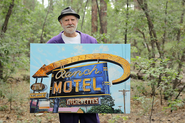 James 'Kingneon' Gucwa holding his painting, 'Ranch Motel' at his studio home.