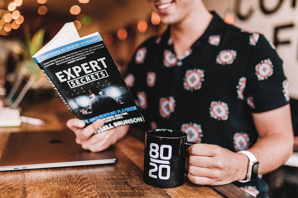 """Homme lisant """"expert secrets"""" et tenant une tasse où il est écrit """"80/20"""""""