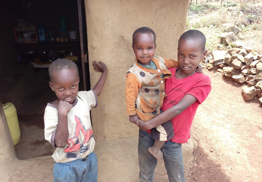 Pictured is a young Kenyan boy holding his youngest brother. They are standing by their other brother in the doorway of this mud hut.