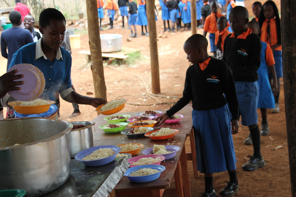 A young Kenyan child wearing her Open Arms Academy uniform reaches for a plate of rice and beans. She is at the front of the line, with many other children behind her.