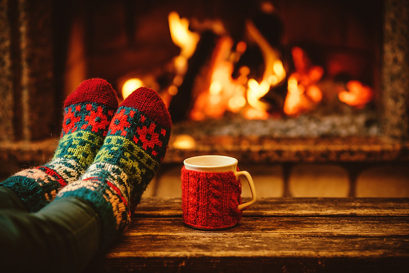 Feet in woollen socks by the Christmas f