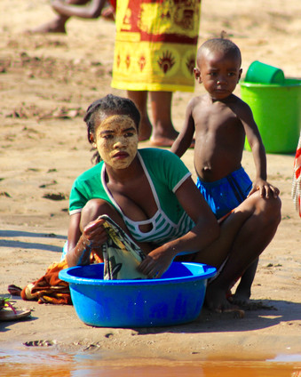 "This mother is washing her clothes on the Mania river. Some Malagasy women paint their faces with beautiful patterns or flower designs in white and yellow paint that provides a stunning contrast to their dark skin. It is a custom associated with the women of the Sakalava tribe. The Vezo women the southern coastal areas of Madagascar paint their faces as well, the Vezo tribe is considered a subset of the Sakalava group. The ""paint"" is actually made from a special type of wood, specifically the bark of a tree that is ground into powder and then mixed into a paste."