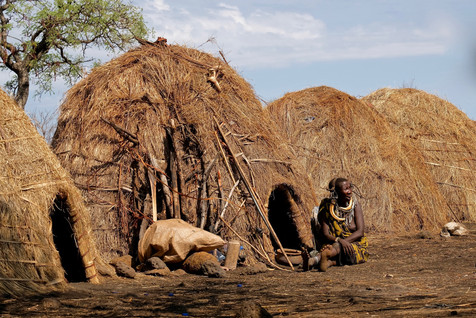Mursi houses with a mursi lady resting on the ground.