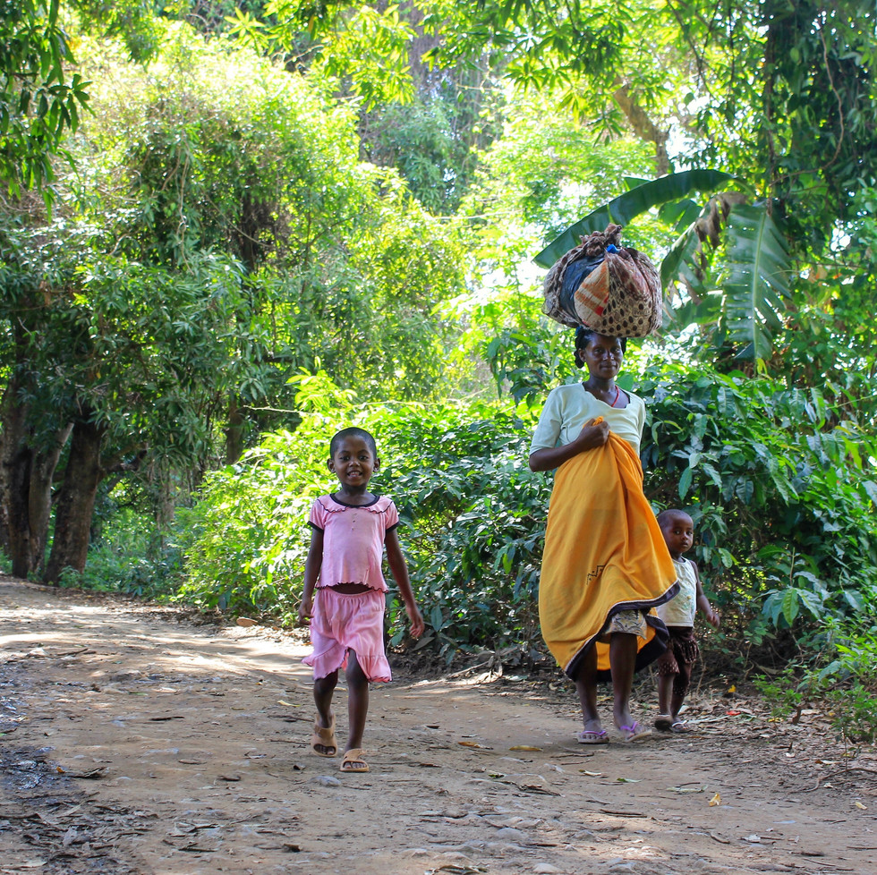 A family walking to the river. While mama is balancing the laundry on her head, her kids are obediently walking besides her. The locals walk a lot of kilometers on their bare feet to catch water or buy/sell their homemade products at the market. Can you imagine that you are following the same track as these people?