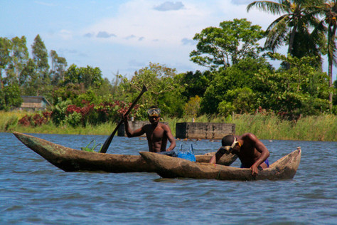 Malagasy man on sea in traditional handmade dugout wooden boat.