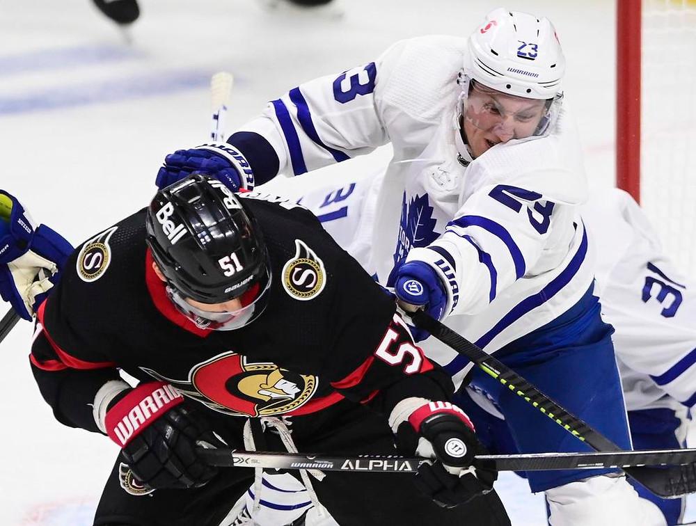 Leafs defenceman Travis Dermott mixes it up with Artem Anisimov Friday night in Ottawa, in the Senators' season opener with Toronto.