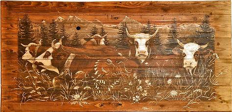 Vaches peintes couchées dans l'herbe.
