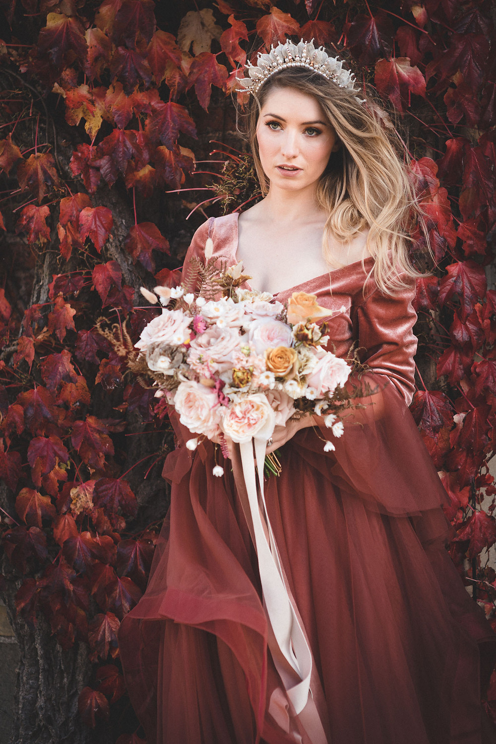 Bride wearing a modern crown stands in front of a red Virginia Creeper holding a bouquet of David Austin roses