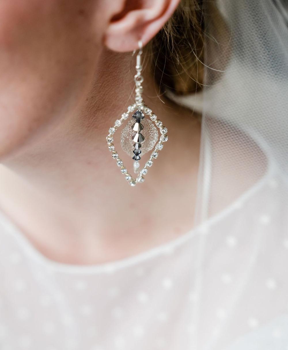 Close up on modern metallic silver crystal chandelier earrings