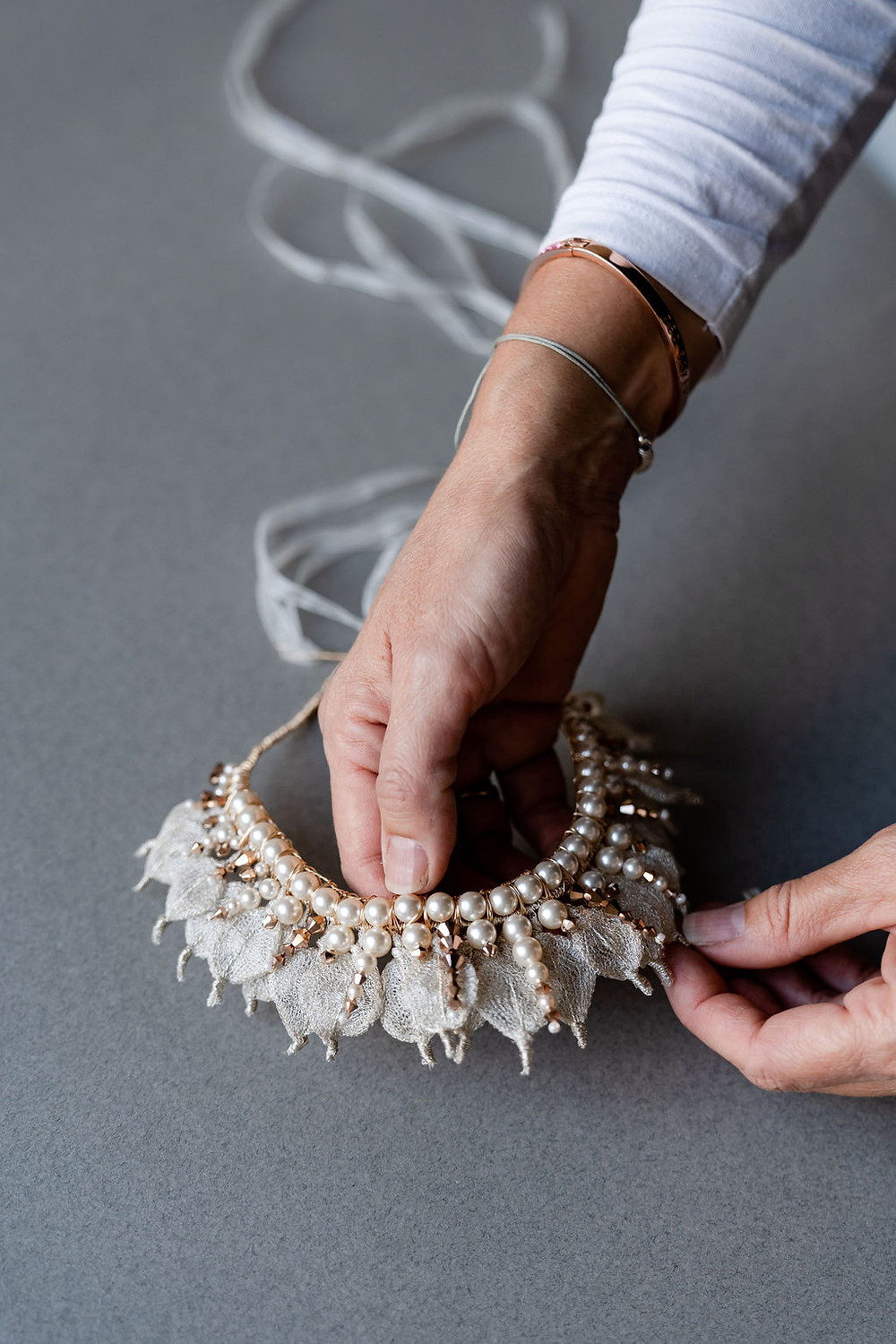 Close up on hands of Cheshire wedding accessory designer, Glorious by Heidi, handling a silver and gold wedding crown