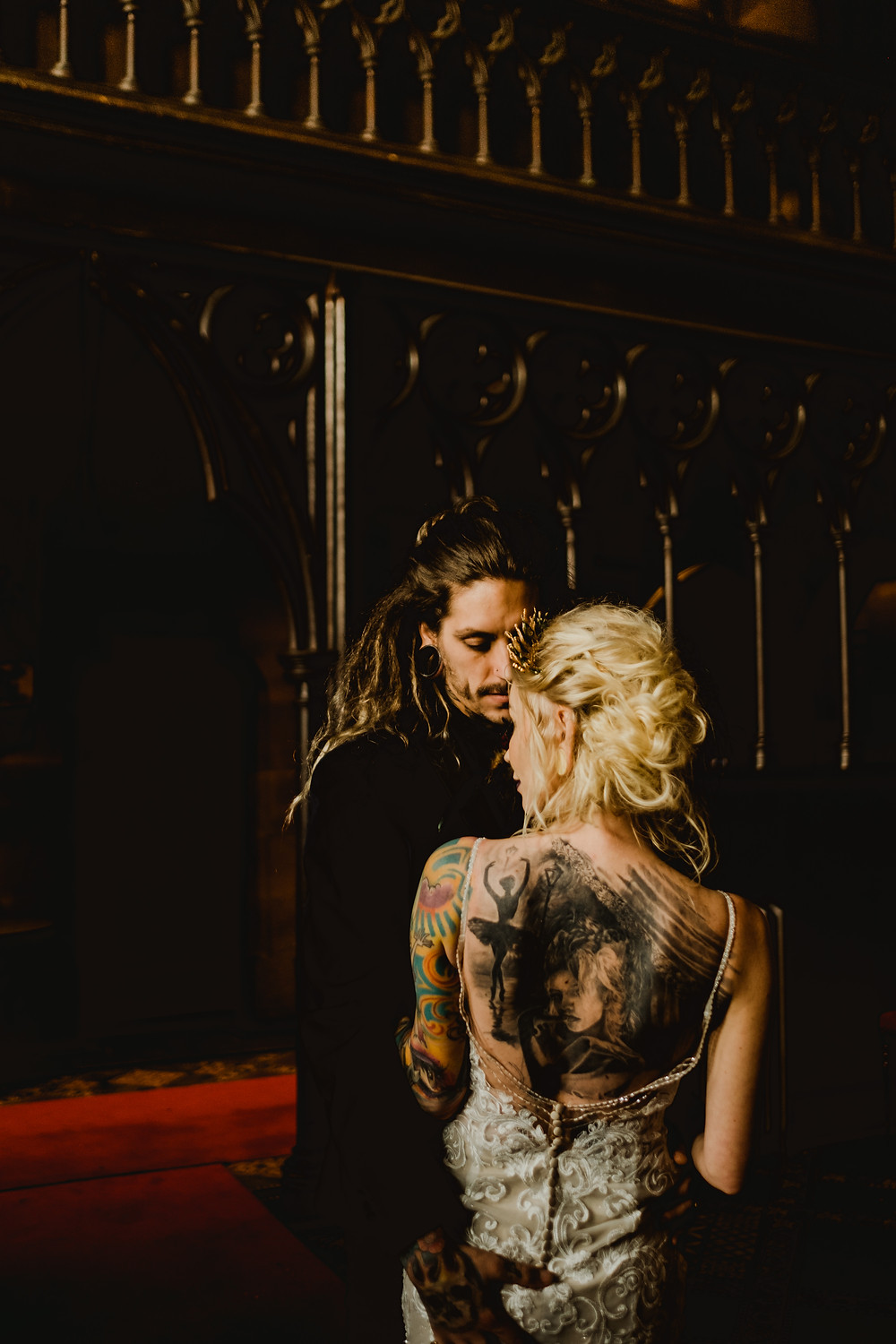 Gothic castle wedding, Cheshire UK. Tattooed bride and groom. Essence of Australia wedding dress from Cheadle Bride. Gold wedding crown. Gold bridal crown. Cheshire wedding accessories.