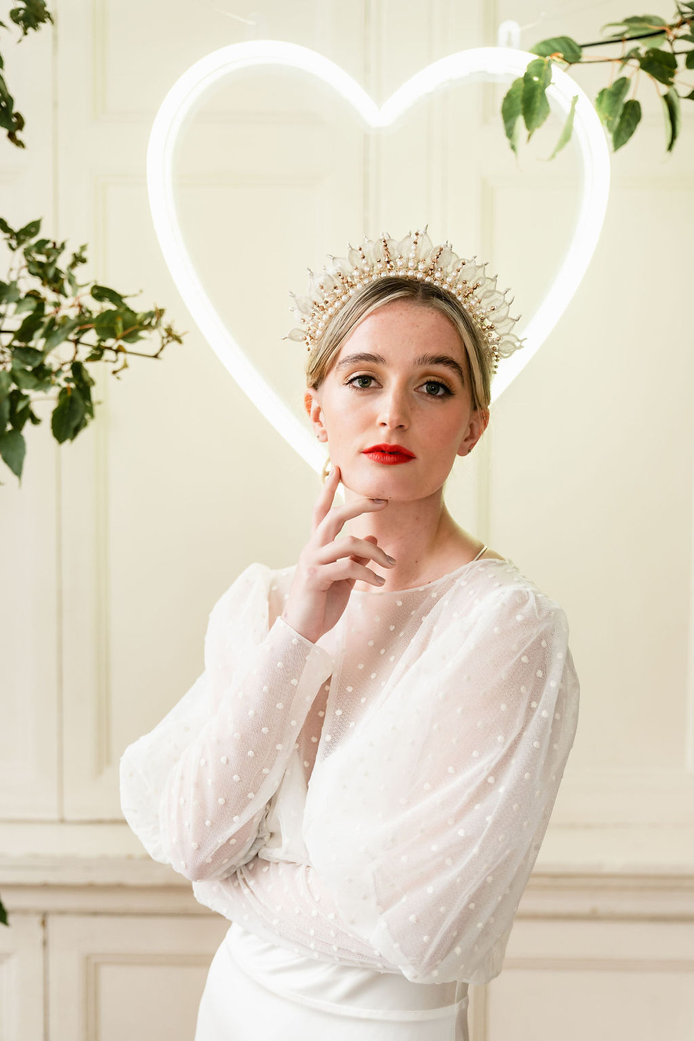 Bride stands in front of a neon heart wearing a statement wedding crown