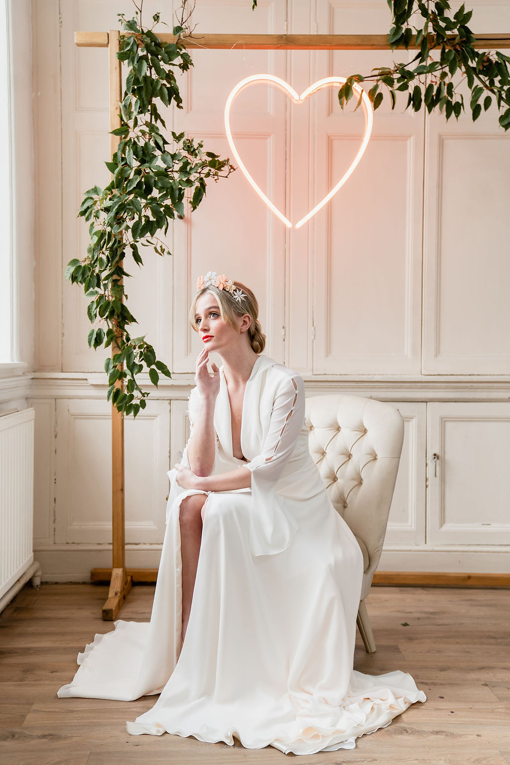 Bride seated under peach neon heart wearing peach, apricot and sky blue hand beaded wedding crown