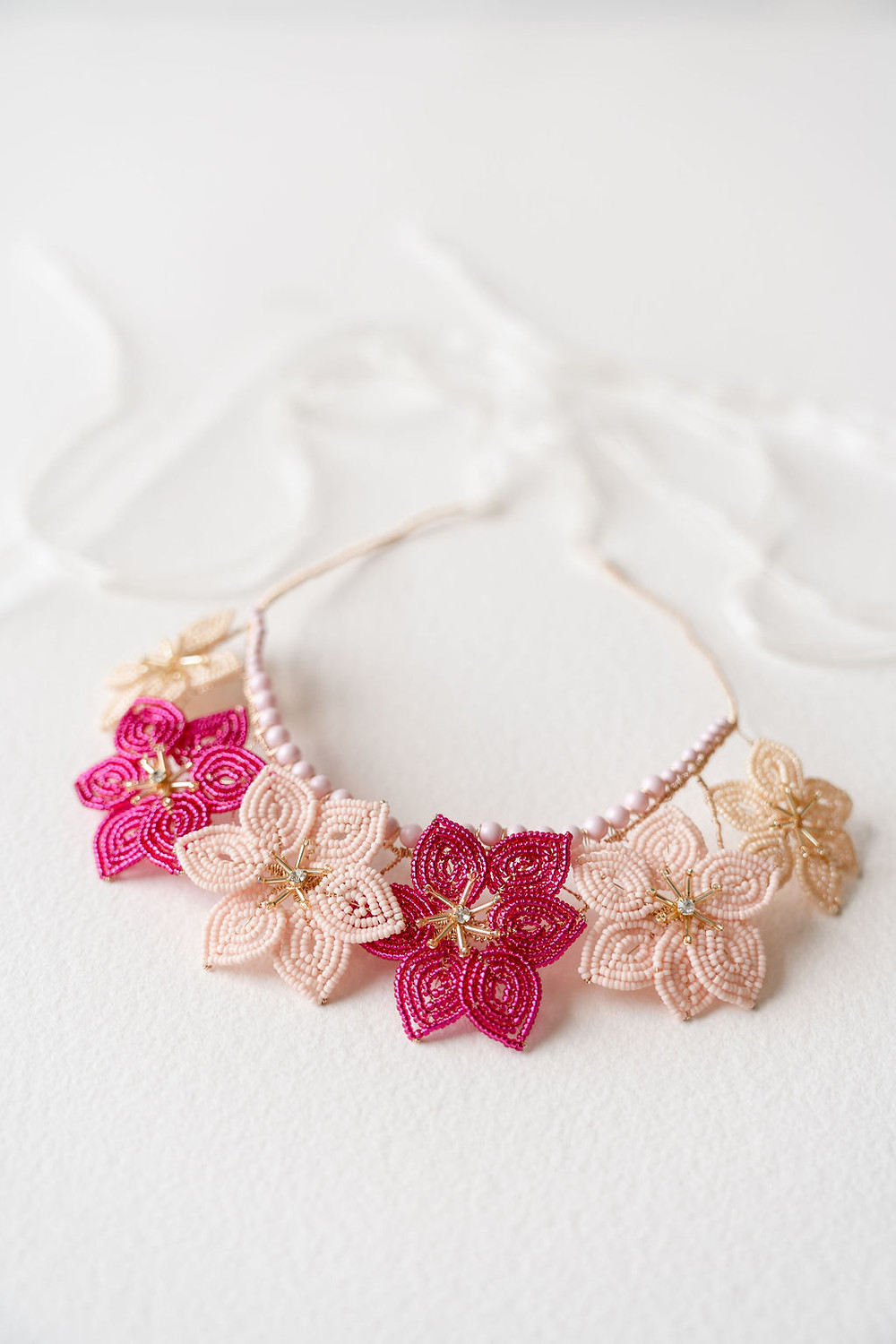 Close up of a pink toned hand beaded bridal flower crown