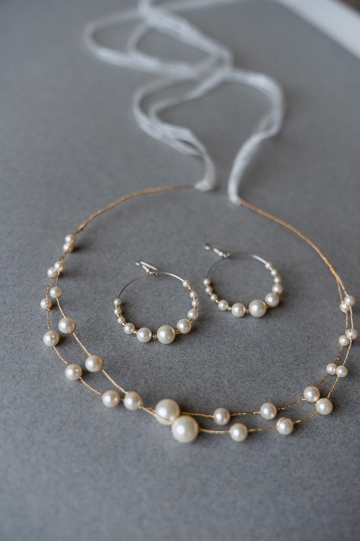 Close up on pearl bridal headband and pearl hoop earrings