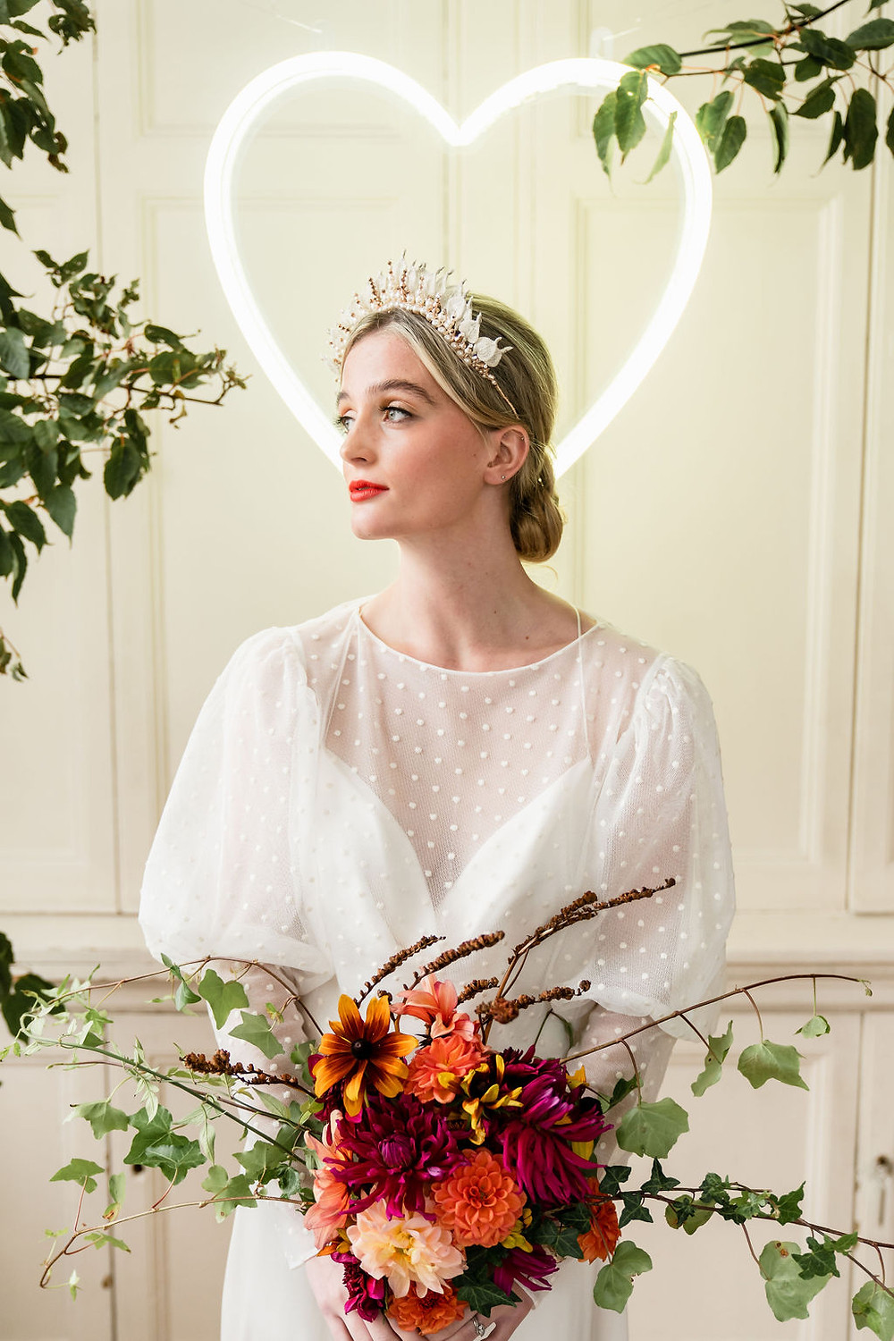 Bride stands in front of neon heart holding a pink, peach and apricot Dahlia bouquet wearing a statement gold and silver bridal crown