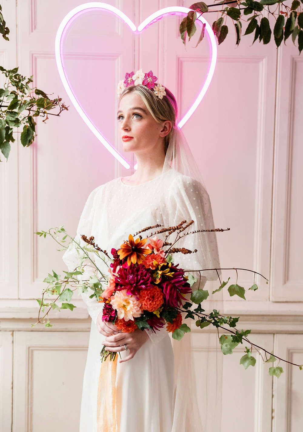 Bride wears a pink toned hand beaded flower crown and stands in front of a neon heart installation whilst holding a bouquet of pink, peach and apricot Dahlia