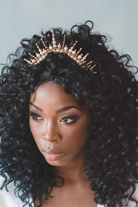 Black bride with natural curly hair wearing a gold wedding crown