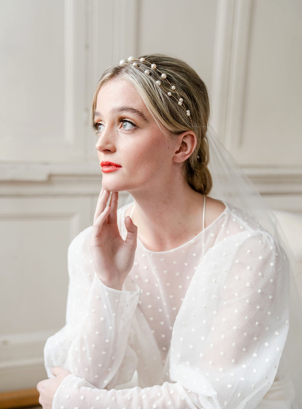 Bride looks out of a window whilst wearing a double strand pearl headband and ivory veil