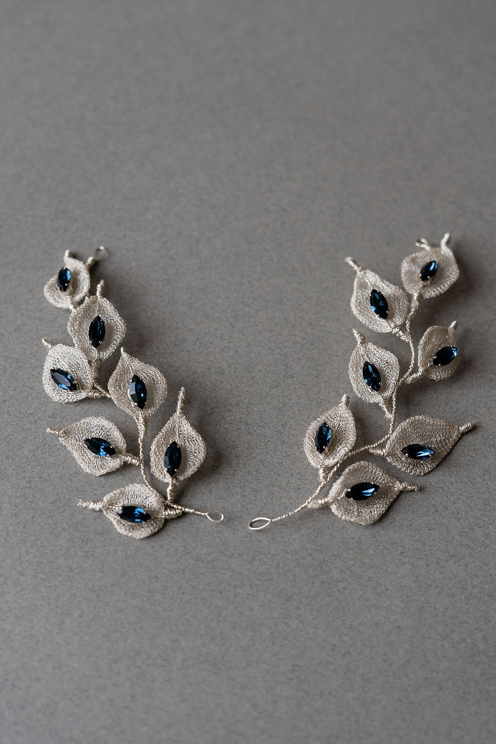 Bridal poytail accessorised with a duo of symmetrical silver leaves and sapphire crystal hair accessories