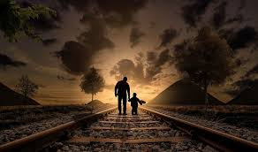 Father and son walking into the sunset holding hands in the manner that God leads us in our purpose.