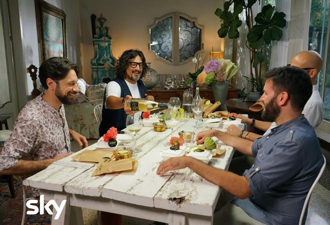 Alessandro Borghese fa il padrone di casa versando il vino ai parteciparti della nuova stagione di 4 RISTORANTI, la prima puntata sarà sul Delivery
