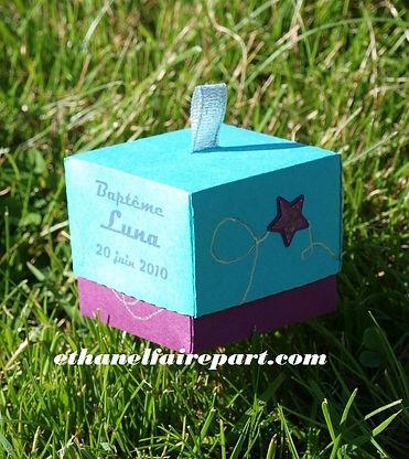 Boite à dragées baptême Galaxie: Etoiles sur boite cube vert lagon, cassis et ruban de satin argenté.
