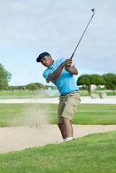 A golfer plays a bunker shot