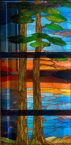 a colorful stained glass image of trees and water by Anne Ryan Miller
