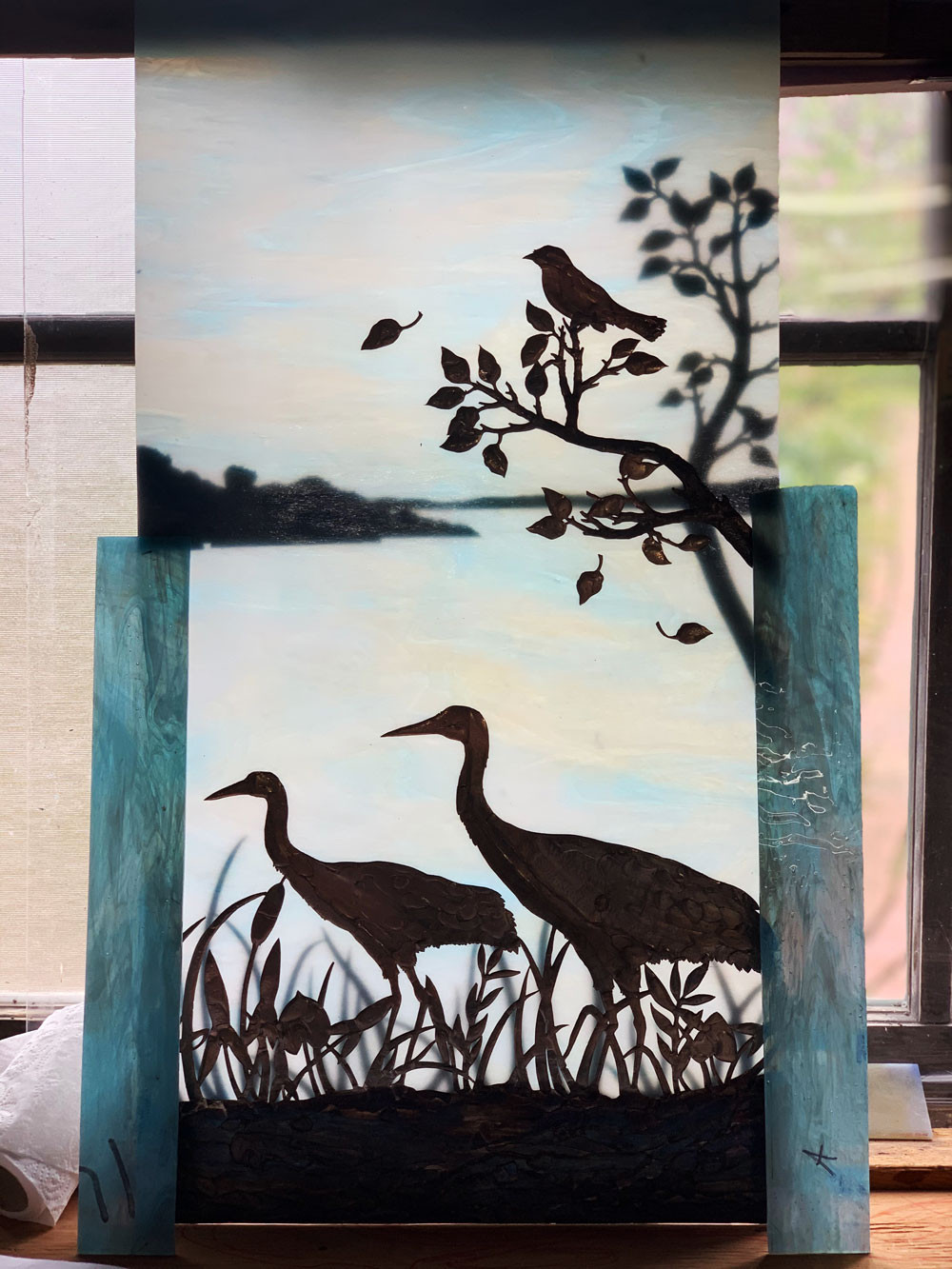 stained glass piece of three birds by the water. ©Anne Ryan Miller